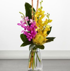 Yellow and pink flower orchids arrangement in a transparent vase